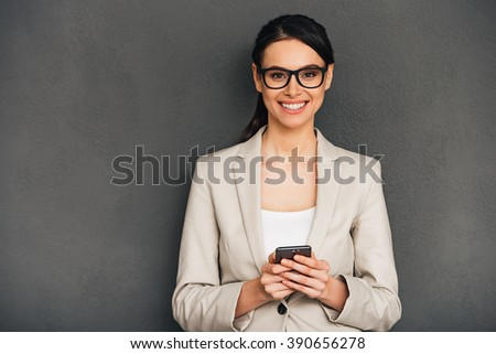 Great news! Beautiful young cheerful businesswoman holding her smart phone and looking at camera with smile while standing against grey background - stock photo