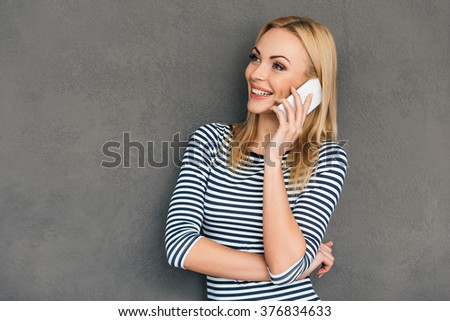 Great news! Beautiful young woman talking on mobile phone and looking away with smile while standing against grey background