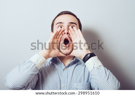 Great news! Cheerful young man in holding hands near mouth and shouting while standing against a gray background