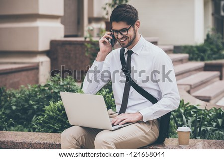 Great news! Confident young man in glasses using his laptop and talking on mobile phone with smile while sitting outdoors - stock photo