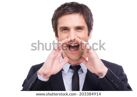 Great news! Happy young man in formalwear shouting while looking at camera and standing isolated on white background  - stock photo