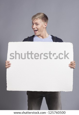 Great news: Happy young man showing white empty panel with space for text isolated on grey background. - stock photo