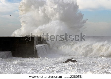 Great ocean wave crashing against pier in Portugal - stock photo
