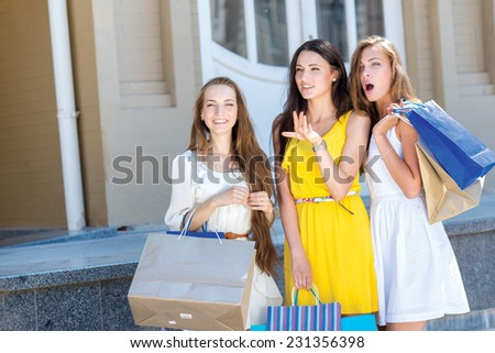 Great option in a shop. Three young and pretty girls are standing with shopping bags in front of the shop window and looking on a great sales offer - stock photo