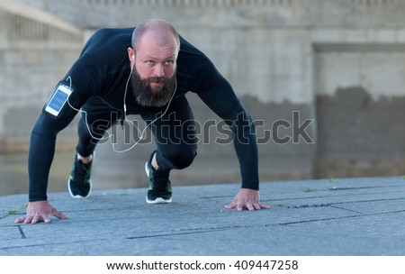 Great outdoor workout. Portrait of muscular professional bodybuilder and fitness trainer. Muscular male sportsman is training himself. Gym fitness sport muscle concept. - stock photo