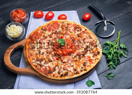 Great pizza bolognese on a circular wooden board on a dark black background, cherry tomatoes, parsley, grated mozzarella cheese, sauce - stock photo