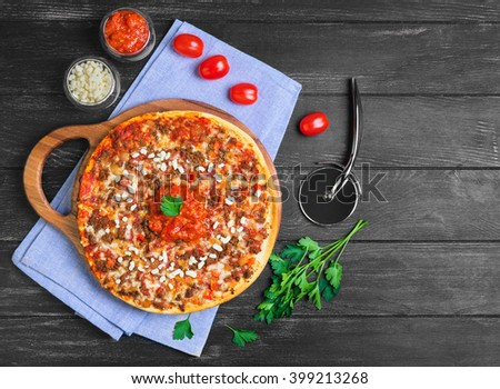 Great pizza bolognese on a circular wooden board on a dark black background, cherry tomatoes, parsley, grated mozzarella cheese, sauce, top view - stock photo