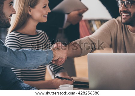 Great pleasure to work with you! Close-up part of two men shaking hands and looking at each other with smile while sitting at the business meeting with their coworkers - stock photo
