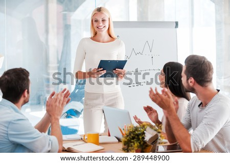 Great presentation! Cheerful young woman standing near whiteboard and smiling while her colleagues sitting at the desk and applauding - stock photo
