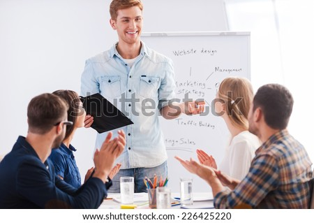 Great presentation! Group of business people in smart casual wear sitting together at the table and applauding to their colleague standing near whiteboard and smiling - stock photo