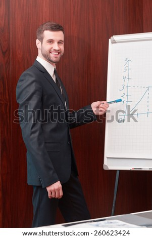 Great presentation. Handsome man in suit and necktie standing near whiteboard and pointing it with smile  - stock photo