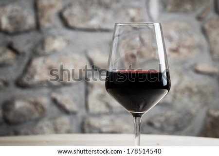 Great red wine glass with restaurant background - stock photo