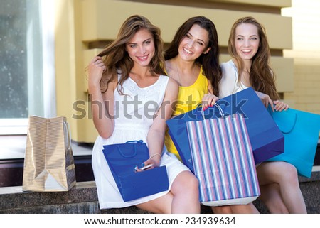 Great shopping day with friends, shops and sales. Three young and attractive women are sitting with shopping bags. Pretty girls are having rest after successful shopping day in a mall - stock photo