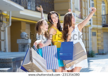 Great shopping moment. Three young and pretty girls are standing with shopping bags and taking photos on mobile phone. All are smiling and having great fun - stock photo