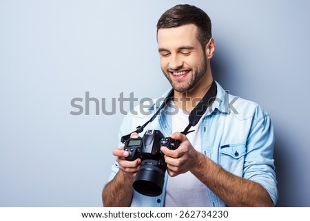 Great shot! Handsome young man holding digital camera and looking at it with smile while standing against grey background