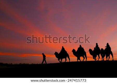 great sky and caravan travelers riding camels