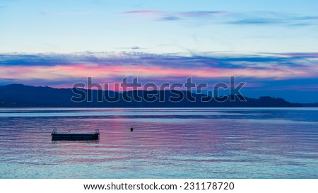 Great sky and cloudscape in the evening after sunset over the lake. swinging board jump - stock photo