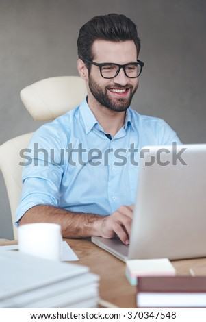 Great solution. Close-up cheerful young handsome man wearing glasses working on laptop and smiling while sitting at his working place - stock photo