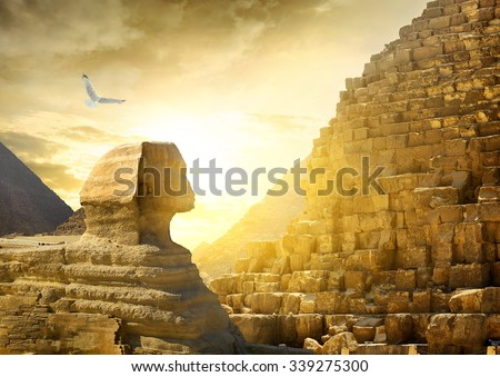 Great sphinx and pyramids under bright sun - stock photo