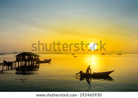 great sunrise and silhouette traditional fisherman at the beach - stock photo
