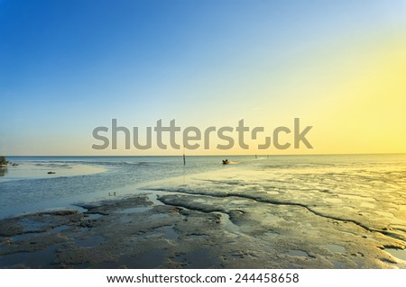 great sunset and blue sky at sunset at muddy beach with fishing boat - stock photo