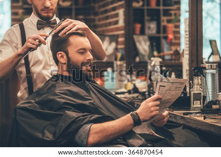 Great time at barbershop. Cheerful young bearded man getting haircut by hairdresser and reading newspaper while sitting in chair at barbershop - stock photo