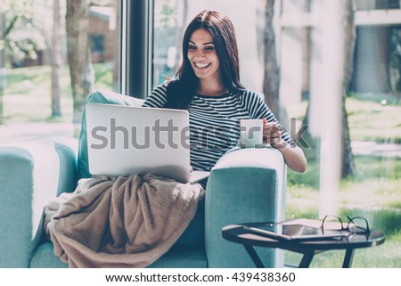 Great time at home. Beautiful young smiling woman working on laptop and drinking coffee while sitting in a big comfortable chair at home  - stock photo