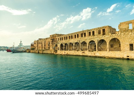 great view of Maltese fort wall with arches near port in Valletta from the sea