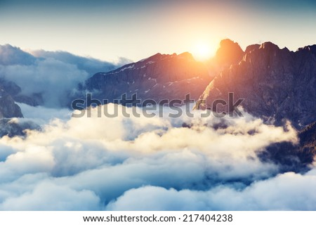 Great view of the foggy Val di Fassa valley with passo Sella. National Park. Dolomites, South Tyrol. Location Canazei, Campitello, Mazzin. Italy, Europe. Dramatic scene. Beauty world. - stock photo