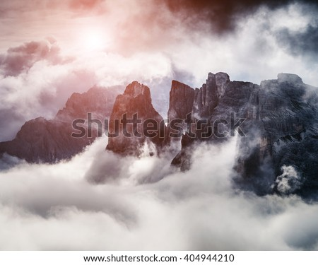 Great view of the foggy valley. Clouds covered the mountain range. Dramatic scene. Location: National Park Tre Cime di Lavaredo, Locatelli. Dolomites Alps, South Tyrol. Italy, Europe. Beauty world. - stock photo