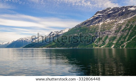 Great view on the mountain peaks with snow caps with the blue surface of the water and wonderful feather clouds on the sky, Norway, Hardangerfjorden