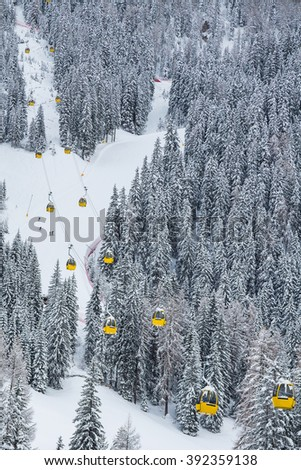 Great view on the mountain ski slope with skiers among the trees and cable cars (ski lifts)  going up and down  - stock photo