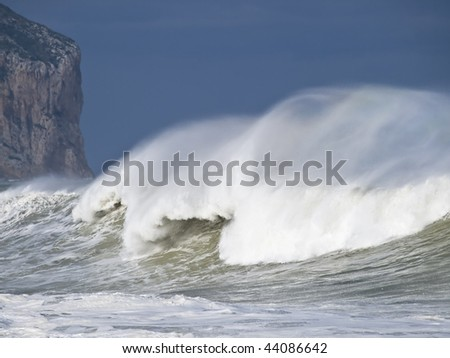 Great wave breaking at sea during a heavy storm, with wind blowing on the foam of the wave crest. In the background is the wall of a mountain cliff