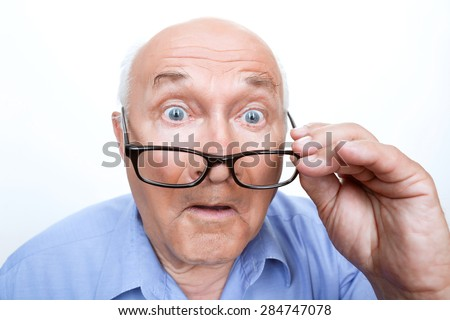 Great wonder. Close up of astonished grandfather holding glasses and looking straight.