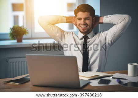 Great work! Handsome young cheerful man keeping hands behind head and smiling while sitting at his working place - stock photo