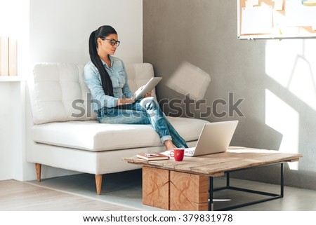 Great working day. Beautiful young woman in glasses working with touchpad while sitting on the couch in office - stock photo