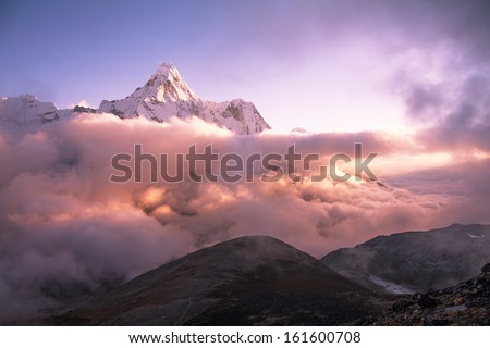 Greatness of nature. Ama Dablam peak (6856 m) above the clouds at sunset. Nepal, Himalayas. Canon 5D MkII. - stock photo
