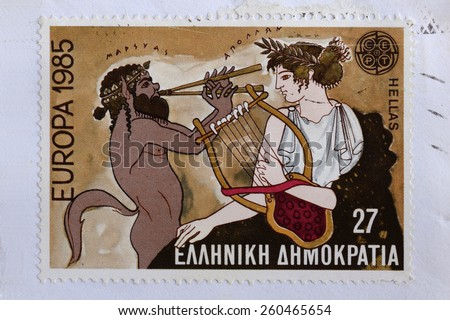 GREECE - CIRCA 1985: Marsyas greek mythology satyr plays aulos double flute on music challenge against Apollo ancient god of music and the arts. Illustration on vintage Hellenic Post postage stamp.