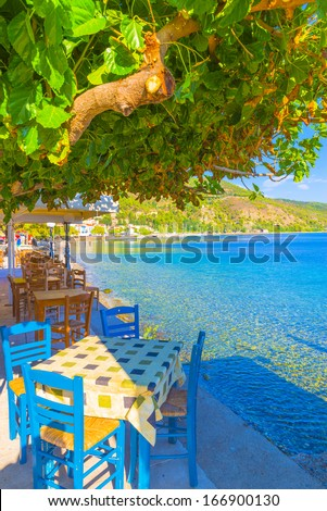 Greece Evoia lake, colorful chairs of a coffee shop by the sea at summer - stock photo