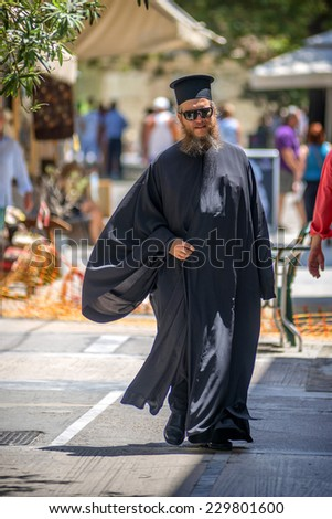 GREECE - JULY 17: A greek orthodox priest walking down the street, on July 17, 2014 in Athens, Greece - stock photo