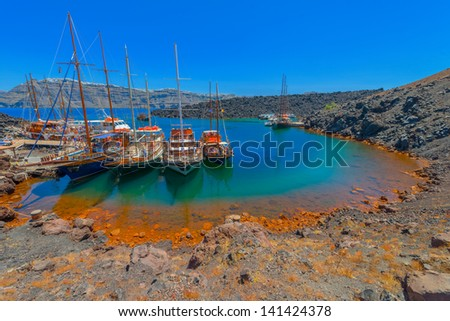 Greece Santorini island in Cyclades,  beautiful  wide view of the sea of volcano with tourist cruise boats - stock photo