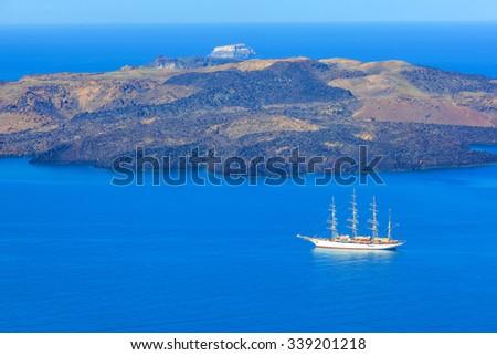 Greece Santorini island in cyclades, sail cruise ships on the sea - stock photo