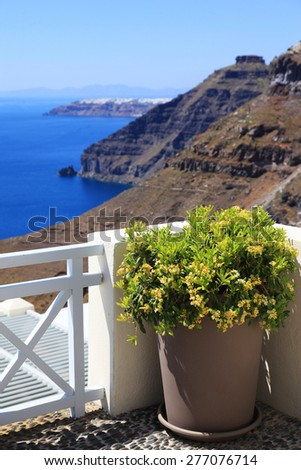 Greece Santorini island in Cyclades, traditional detail sights of colorful flowers with pots and caldera sea in background - stock photo