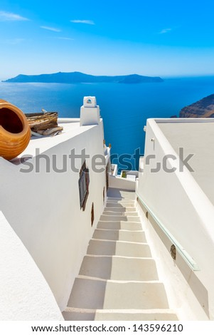 Greece Santorini island in Cyclades, traditional sights of colorful and white washed walk paths like narrow streets and caldera sea in background - stock photo
