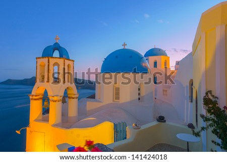 Greece Santorini island in Cyclades,  wide view of white washed colorful houses at night - stock photo