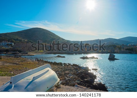 Greece Syros island in Cyclades, Old port view with sun reflecting on sea water with ancient monuments on background - stock photo