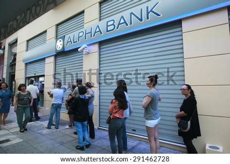 GREECE, Thessaloniki JUNE 28, 2015: Citizens line up to use an automated teller machine (ATM) outside a closed bank. Cash machines ran dry after Greeks rushed to withdraw their savings from the banks. - stock photo