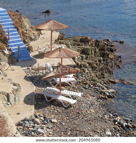 Greece, Tinos island, blue stairs to tranquil beach with umbrellas and chairs - stock photo