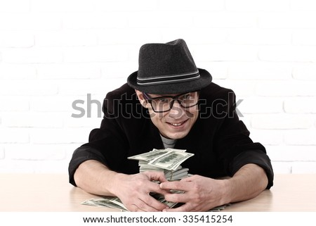 Greed, emotional man in glasses holding bundles of money  - stock photo