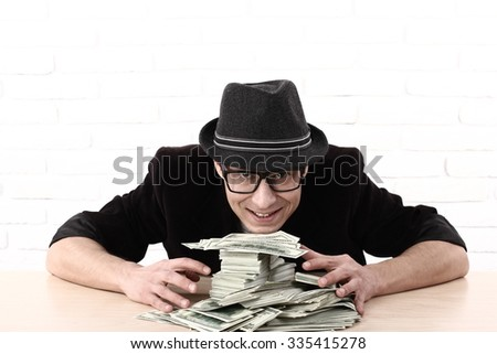 Greed emotional man in glasses holding bundles of money  - stock photo